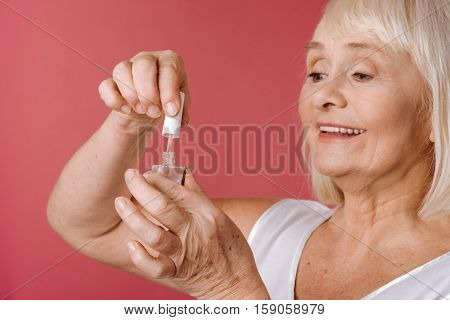 Home manicure. Content retired good looking woman opening a bottle of nail varnish and using it while doing her manicure at home