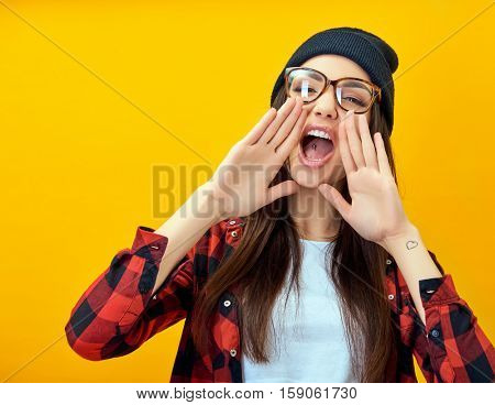 Hipster girl screaming like in megaphone holding hands near her face with open mouth. Young woman touts everyone over yellow background.