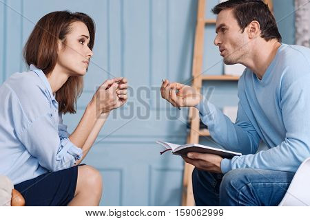 Speak about your problems. Desperate young woman feeling depressed and sitting in the arm chair while solving her problems with professioanl psychotherapist