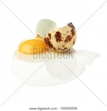 Single cracked raw quail egg with yolk isolated over white background