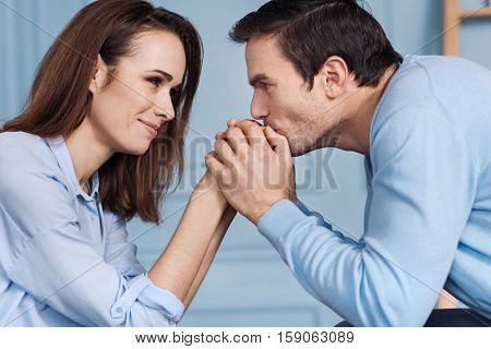 My dear Delighetd handsome man kissing hand of his beautiful wife and looking at her while expressing love