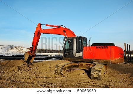 Heavy big red excavator working on new construction site