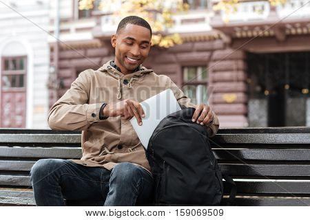 Photo of young happy african man getting laptop from backpack. Look at laptop.