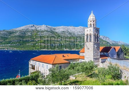 View at mediterranean landscape with Dominican Monastery in town Korcula with surfing place Viganj in background, Croatia summertime, Europe.