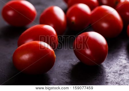 Detail Of Several Red Cherry Tomatoes On Black Board