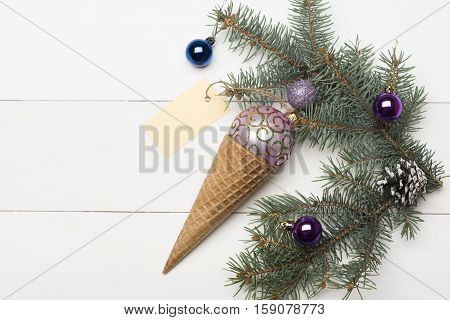 Christmas baubles and decorations including ice cream cone rose gold christmas ball yellow tag christmas tree with brown pine cone and balls on vintage white background