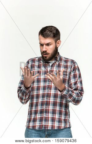 Man wearing a checkered shirt is looking scared with an imaginary object in his hands. Over white background