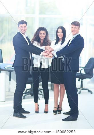 Group of business people piling up their hands together in the w