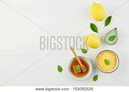 Homemade lemon salt bath and fresh honey in the plate with honeycomb and wooden dipper on rustic white background from top view. Flat lay good for background and space.