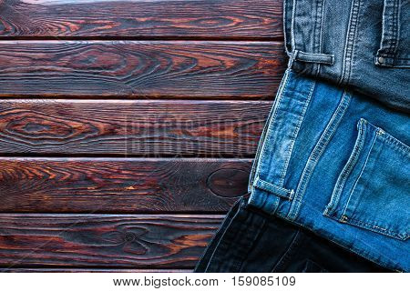 Jeans Of Different Colors On A Wooden Background And Space For Text
