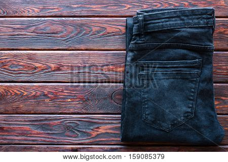 Black Jeans Folded On A Wooden Background