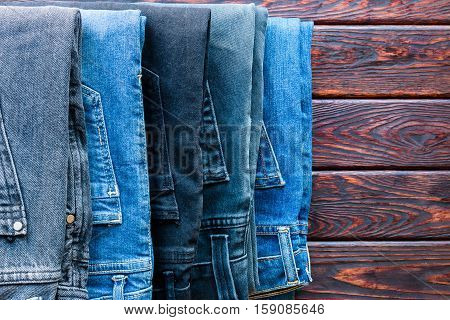 Stack Of Different Jeans And A Place For Text On Wooden Background