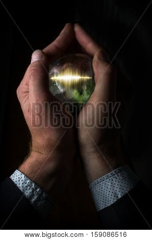 Holding magic crystal ball containing sound wave