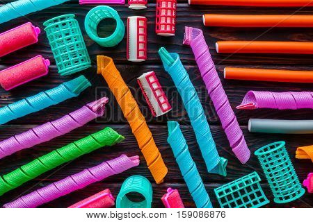 Different Colorful Curlers On A Wooden Background