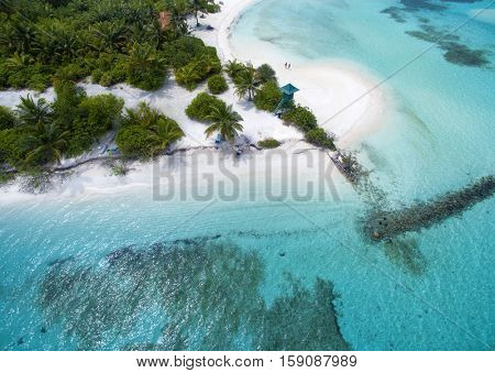 Two tiny people standing at the white sand beach. Landscape seascape aerial view over a Maldives Male Atoll island. Beach with lifeguard tower seen from above.