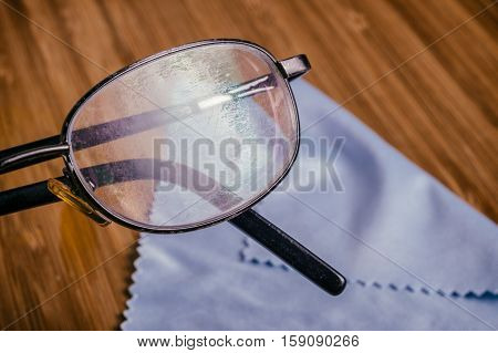 Old Eyeglass with many scratches and blue microfiber cloth