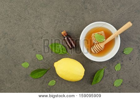 Homemade Lemon Essential Oil, Salt Bath And Fresh Honey In The Plate With Honeycomb, Dipper And Mint
