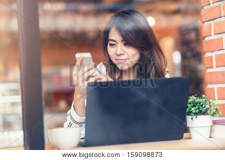 Viewed through glass with reflections of happy beautiful young Asian woman smile while using smart phone mobile with laptop at cafe