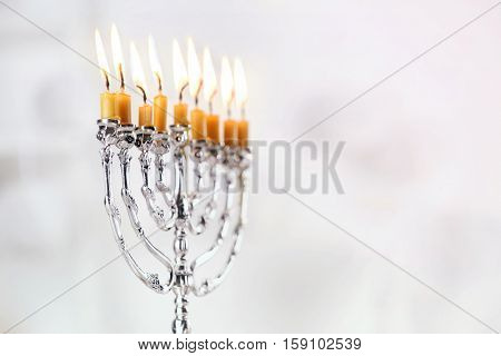 Beautiful menorah with burning candles on light blurred background. Hanukkah concept