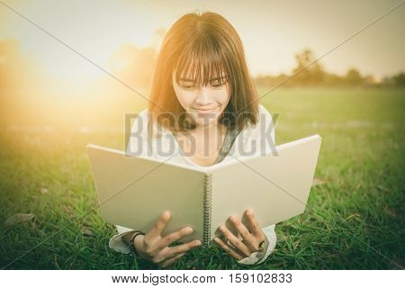 Young Girl With Book In The Green Garden