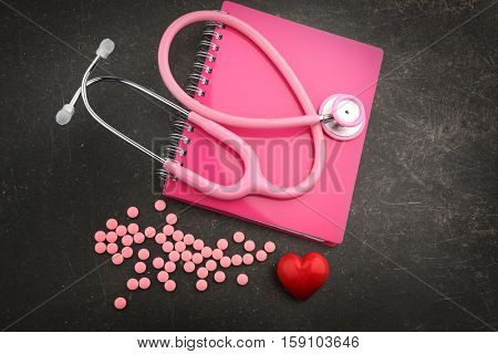 Notebook, stethoscope, red heart and pills on dark background