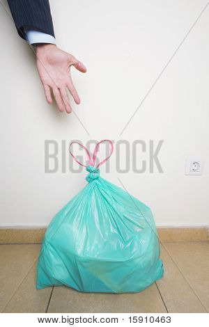 Hand Reaching For Green Plastic Bag