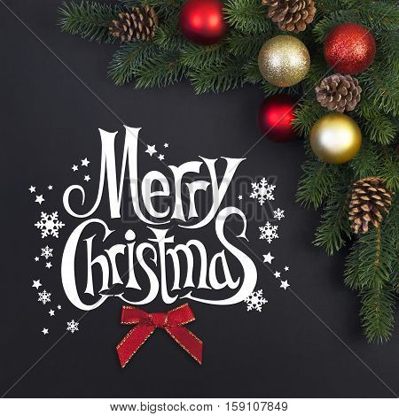 Christmas fir branch with Pine cones on a Black background with the wishes of Merry Christmas 2017