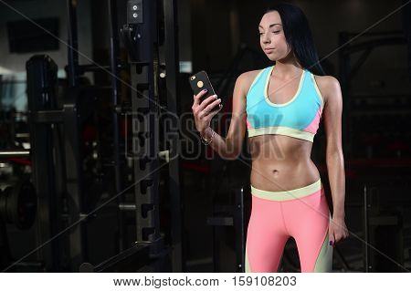 Fit Woman In Gym Holding Smart Phone