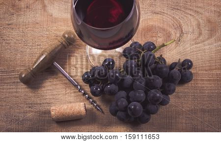 Glass Of Red Wine With A Sprig Of Grapes On A Wooden Table.