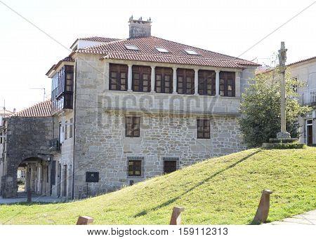 Stone cross on grass next to a building in Pontevedra Galicia Spain