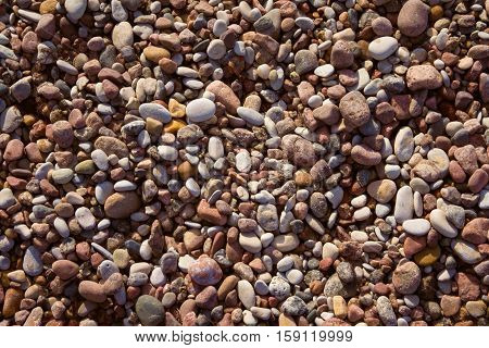 marine pebbles on the shore of the Baltic Sea, to grind with water in various sizes and colors, the oval and round,  nature, background tinted, preset, yellow tint