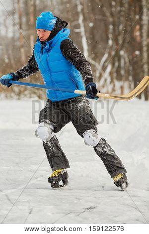 Young man plays hockey at outdoor skating rink in park.