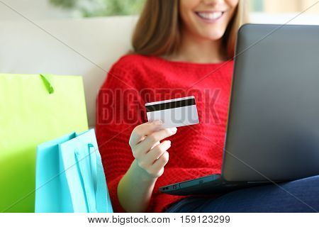 Close up of a girl hand holding a credit card and buying on line with a laptop and shopping bags beside