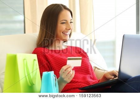 Portrait of a woman shopping on line holding a credit card and typing in a laptop sitting on a couch in the living room at home
