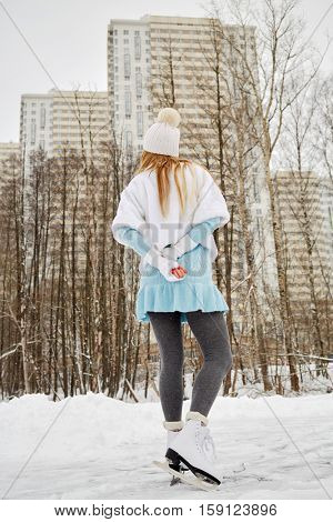 Young woman skates at outdoor skate rink in winter park against highrise buildings, rear view.
