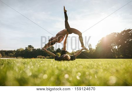 Young Couple Doing Acrobatic Yoga On Lawn