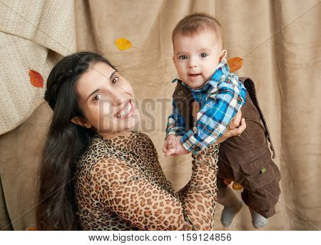 autumn woman with little boy on yellow fall leaves, apples, pumpkin and decoration on textile, happy family and country concept