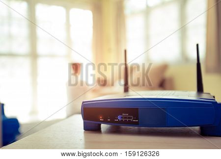 closeup of a wireless router and a young man using Laptop and notebook computers on living room at home with a window in the background