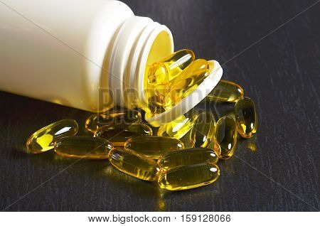 Fish oil omega 3 capsules in container and near on black stone background close up