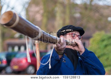 OLDENZAAL NETHERLANDS - NOVEMBER 27 2016: Unknown man blowing a so called