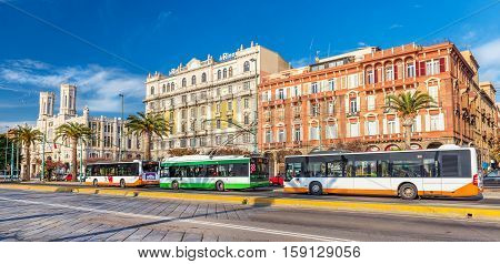Cagliari, Sardinia - January 2016, Italy: Beautiful colorful buildings on Cagliari seafront, buses and trolley car parked near bus stop on central street of the city