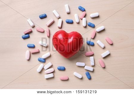 Red heart with pills on table