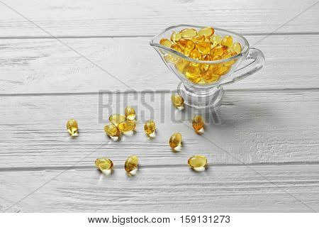 Glass bowl with cod liver oil pills on white wooden table