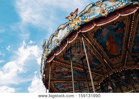 Children's Carousel against the blue sky with clouds