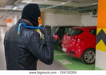 Thief in balaclava holds crowbar in hand and is going to steal a car from parking lot.