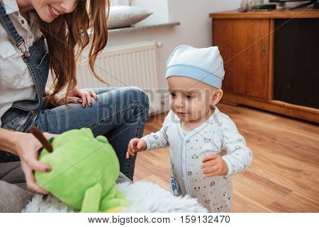Smiling young mother sitting and playing with her little son at home
