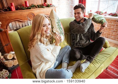 Side view of happy couple in sweater sitting and indulge on sofa