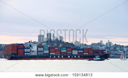 San Francisco CA - November 27 2016: Tugboat Z-THREE assisting cargo ship YM ELIXIR to maneuver through the San Francisco Bay after departing the Port of Oakland. City in the background at sunset.