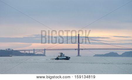 San Francisco CA - November 27 2016: Tugboat Z-THREE in the San Francisco Bay heading towards the Golden Gate Bridge sun setting in the background.