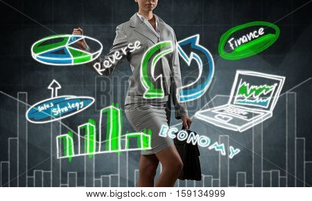 Close view of businesswoman drawing colorful diagrams and graphs on screen